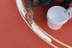 Εργαζόμενος που χρωματίζει το περιθώριο στο πάτωμα για το υπαίθριο στάδιο Στοκ εικόνα με δικαίωμα ελεύθερης χρήσης