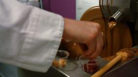 Εργαζόμενος που ψεκάζει τα καρύδια πάνω από τη λειωμένη σοκολάτα απόθεμα βίντεο