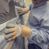 Εργαζόμενος που ωθεί το κεραμίδι στο τσιμέντο στον τοίχο στοκ φωτογραφία με δικαίωμα ελεύθερης χρήσης