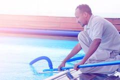 Εργαζόμενος προσωπικού ξενοδοχείων που καθαρίζει τη λίμνη συντήρηση Στοκ εικόνες με δικαίωμα ελεύθερης χρήσης