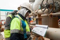 Εργαζόμενος σε ένα εργοτάξιο οικοδομής που φαίνεται έγγραφα Στοκ εικόνα με δικαίωμα ελεύθερης χρήσης