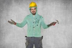 Εργαζόμενος σε ένα κράνος και με ένα σφυρί στο χέρι του Στοκ Εικόνες