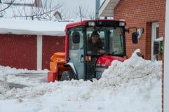Εργαζόμενος σε ένα οργώνοντας χιόνι τρακτέρ μετά από μια χιονοθύελλα Στοκ Εικόνες