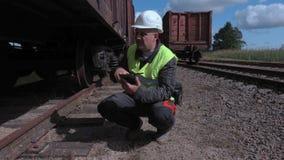 Εργαζόμενος σιδηροδρόμων που χρησιμοποιεί την ταμπλέτα κοντά στις ρόδες βαγονιών εμπορευμάτων απόθεμα βίντεο