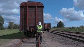 Εργαζόμενος σιδηροδρόμων που χρησιμοποιεί την ταμπλέτα κοντά στο τελευταίο βαγόνι εμπορευμάτων φιλμ μικρού μήκους