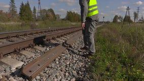 Εργαζόμενος σιδηροδρόμου που μιλά στο έξυπνο τηλέφωνο κοντά στις ράγες φιλμ μικρού μήκους