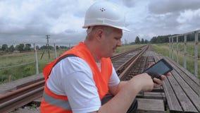 Εργαζόμενος σιδηροδρόμων που χρησιμοποιεί το PC ταμπλετών στη γέφυρα σιδηροδρόμων απόθεμα βίντεο