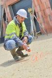Εργαζόμενος στα σημάδια σχεδίων εργοτάξιων οικοδομής στο πάτωμα Στοκ φωτογραφίες με δικαίωμα ελεύθερης χρήσης