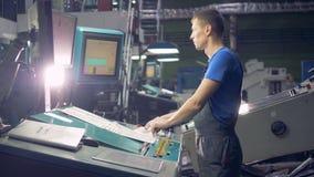 Εργαζόμενος στη βιομηχανική αυτοματοποιημένη μηχανή που λειτουργεί με τη γραμμή εργοστασίων απόθεμα βίντεο