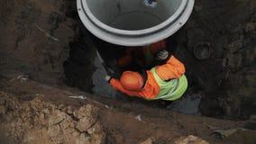 Εργαζόμενος στη σκληρή βελονιά δύο καπέλων συγκεκριμένα δαχτυλίδια καταπακτών αιθουσών με το τσιμέντο απόθεμα βίντεο