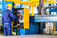 Εργαζόμενος στις εγκαταστάσεις κατασκευής στο πίνακα ελέγχου μηχανών Στοκ εικόνα με δικαίωμα ελεύθερης χρήσης