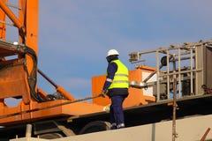 Εργαζόμενος στον κίτρινο και πορτοκαλή γερανό στο εργοτάξιο οικοδομής στοκ φωτογραφίες
