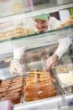 Εργαζόμενος στο αρτοποιείο που παίρνει έξω το κέικ μπισκότων από την προθήκη Στοκ Φωτογραφία