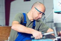 Εργαζόμενος στο εργοστάσιο στον πάγκο εργασίας με το σφυρί Στοκ εικόνα με δικαίωμα ελεύθερης χρήσης