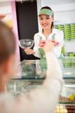 Εργαζόμενος στο κατάστημα ζύμης που προσφέρει τον πελάτη με τα macarons στο πιατάκι Στοκ Εικόνα