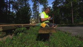 Εργαζόμενος στο πάρκο στον πάγκο που χρησιμοποιεί την ταμπλέτα απόθεμα βίντεο