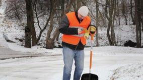 Εργαζόμενος στο πεζοδρόμιο με τον πόνο στην πλάτη το χειμώνα απόθεμα βίντεο