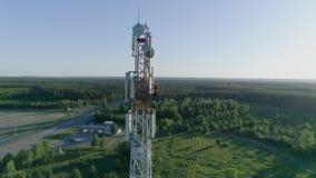 Εργαζόμενος τεχνικών που συντηρεί την κυψελοειδή κεραία, άποψη κηφήνων του πύργου συστημάτων τηλεπικοινωνιών απόθεμα βίντεο
