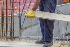 Εργαζόμενος Bulder που πριονίζει τον ξύλινο πίνακα με το πριόνι 3 χεριών στοκ φωτογραφία