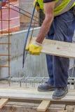 Εργαζόμενος Bulder που πριονίζει τον ξύλινο πίνακα με το πριόνι 2 χεριών στοκ φωτογραφία