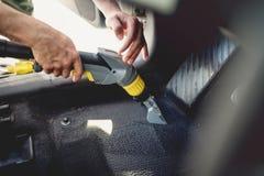 εργαζόμενος, detailer σκουπίζοντας με ηλεκτρική σκούπα τάπητας του αυτοκινήτου εσωτερικός, χρησιμοποιώντας το κενό ατμού στοκ εικόνες με δικαίωμα ελεύθερης χρήσης