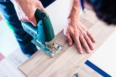 Εργαζόμενος DIY που κόβει την ξύλινη επιτροπή με jig το πριόνι στοκ φωτογραφία