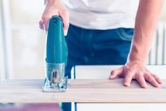 Εργαζόμενος DIY που κόβει την ξύλινη επιτροπή με jig το πριόνι στοκ φωτογραφία με δικαίωμα ελεύθερης χρήσης