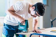 Εργαζόμενος DIY που κόβει την ξύλινη επιτροπή με jig το πριόνι στοκ εικόνα με δικαίωμα ελεύθερης χρήσης