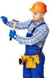 Εργαζόμενο άτομο με το σφυρί που οδηγεί ένα καρφί στον τοίχο Στοκ φωτογραφία με δικαίωμα ελεύθερης χρήσης