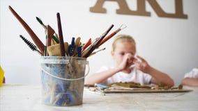 Εργαλεία για στο εργαστήριο τέχνης με το θολωμένο κορίτσι παιδιών στο υπόβαθρο απόθεμα βίντεο