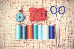 Εργαλεία για τη ραπτική, κόκκινο πλεκτό μαξιλάρι βελόνων για το ράψιμο, ψαλίδι και χρωματισμένες σπείρες νημάτων στο καφετί υπόβα στοκ φωτογραφία