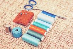 Εργαλεία για τη ραπτική, κόκκινο πλεκτό μαξιλάρι βελόνων για το ράψιμο, ψαλίδι και χρωματισμένες σπείρες νημάτων στο καφετί υπόβα στοκ εικόνες