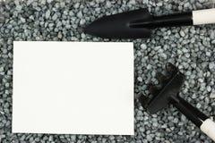 Εργαλεία κήπων στο αμμοχάλικο Ένα φτυάρι και μια τσουγκράνα στο έδαφος στοκ εικόνα με δικαίωμα ελεύθερης χρήσης