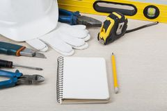 Εργαλεία κατασκευής και άσπρο κράνος στο ξύλινο υπόβαθρο χρυσά πλήκτρα σπιτιών δάχτυλων κατασκευής έννοιας Στοκ εικόνες με δικαίωμα ελεύθερης χρήσης