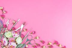 Εργαλεία μανικιούρ σε ένα ρόδινο υπόβαθρο που διακοσμείται με τα λουλούδια στοκ εικόνα με δικαίωμα ελεύθερης χρήσης