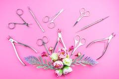 Εργαλεία μανικιούρ σε ένα ρόδινο υπόβαθρο που διακοσμείται με τα λουλούδια στοκ φωτογραφίες