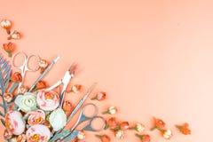 Εργαλεία μανικιούρ σε ένα ρόδινο υπόβαθρο που διακοσμείται με τα λουλούδια στοκ φωτογραφία