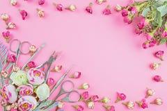 Εργαλεία μανικιούρ σε ένα ρόδινο υπόβαθρο που διακοσμείται με τα λουλούδια στοκ εικόνες