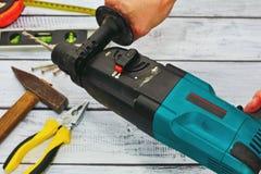 Εργαλεία χεριών και μηχανή διατρήσεων στα χέρια Στοκ Φωτογραφία