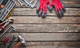 Εργαλείο εργασίας σε έναν ξύλινο πίνακα Πριόνι, σφυρί, κατσαβίδια, πένσες, δεκάρες, μαχαίρι, τοπ άποψη, διάστημα αντιγράφων στοκ φωτογραφία