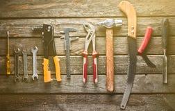 Εργαλείο εργασίας σε έναν ξύλινο πίνακα Πριόνι, σφυρί, κατσαβίδια, πένσες, δεκάρες, μαχαίρι, τοπ άποψη στοκ φωτογραφία