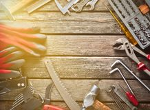 Εργαλείο εργασίας σε έναν ξύλινο πίνακα Πριόνι, σφυρί, κατσαβίδια, πένσες, δεκάρες, μαχαίρι, τοπ άποψη, διάστημα αντιγράφων στοκ εικόνες