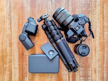 Εργαλείο, κάμερα, τρίποδο, λάμψη και φακοί φωτογραφίας σε ένα ξύλινο υπόβαθρο στοκ φωτογραφία