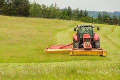 Εργασία για ένα γεωργικό αγρόκτημα Ένα κόκκινο τρακτέρ κόβει ένα λιβάδι Στοκ Εικόνες