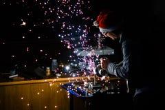 Εργασία για το τιτάνιο με το μύλο γωνίας και Χριστούγεννα beanie στοκ φωτογραφίες