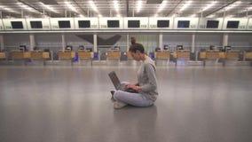 Εργασία γυναικών για το lap-top και αναμονή την πτήση στον αερολιμένα στο τερματικό στο πάτωμα απόθεμα βίντεο