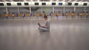 Εργασία γυναικών για το lap-top και αναμονή την πτήση στον αερολιμένα στο τερματικό στο πάτωμα φιλμ μικρού μήκους