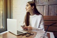 Εργασία γυναικών στον καφέ με το lap-top κοντά στο παράθυρο με τον καφέ latte Στοκ εικόνες με δικαίωμα ελεύθερης χρήσης