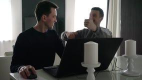 Εργασία δύο νεαρών άνδρων με ένα lap-top απόθεμα βίντεο