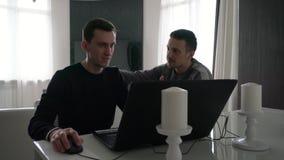 Εργασία δύο νεαρών άνδρων με ένα lap-top φιλμ μικρού μήκους